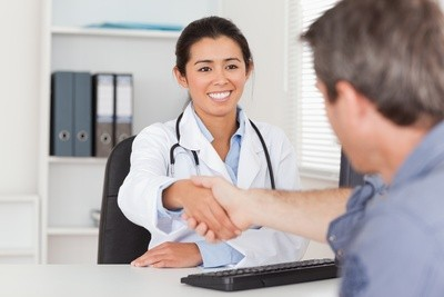 photo of a doctor shaking hands with a patient